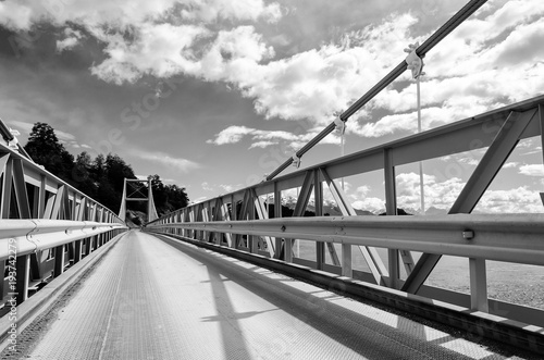 Suspension bridge over the water runoff of General Carrera Lake, near Lake Bertrand, Puerto Tranquilo, Chile Chico, Aysen,  Chile, monochrome.