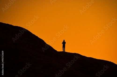 Poster Oranje eclat Silhouette of man on a rock watching the sunset