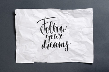 Follow your dreams. Handwritten text on white crumpled paper. Inspirational quote.
