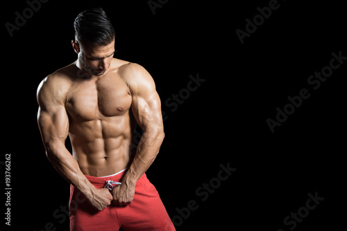 Muscular Men Flexing Muscles On Black Background