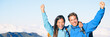 Happy mountain climbers hiking mountains reaching mountain summit cheering with arms up in success. Successful tourists couple trekking in altitude banner panorama.