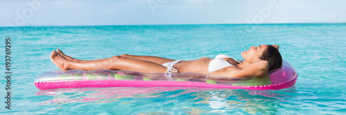 Luxury summer vacation beach woman relaxing lying down on inflatable pool float floating on turquoise ocean sun tanning. Bikini model sleeping on holiday banner panorama.