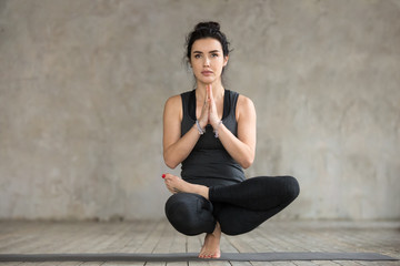 Young sporty woman practicing yoga, doing Half Lotus Toe Balance exercise, Toestand pose, working out, wearing sportswear, black pants and top, indoor full length, gray wall in yoga studio