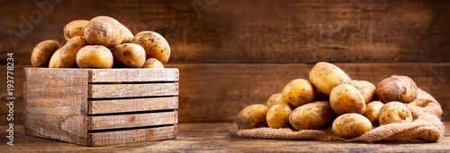 Wall mural fresh raw potatoes in a wooden box
