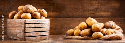 fresh raw potatoes in a wooden box - 193778234