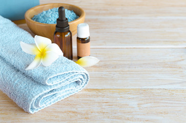 Spa blue sea salt,  relax essential oil, towel with exotic flower frangipani  on wooden background with copy space. .The Health and Wellness Spa concept. © vasanty