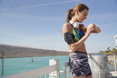 Fitness girl stretching after exercising, Miami South beach pier