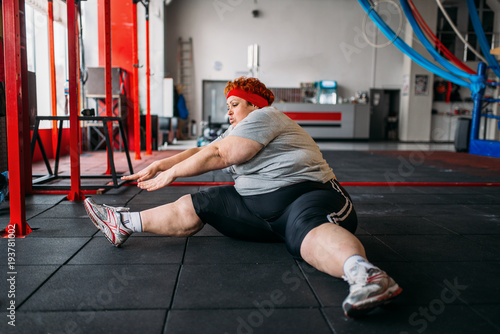 Fat woman exercises on the floor, workout in gym