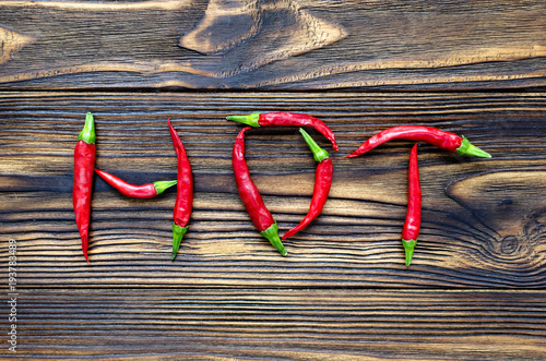 Tuinposter Hot chili peppers word 'hot' from chili peppers on brown wooden background