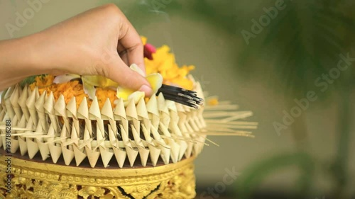 Foto op Plexiglas Indonesië Balinese woman hand adding flowers for daily offerings with incense