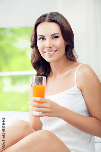 Foto op Canvas Sap Happy smiling young woman drinking orange juice