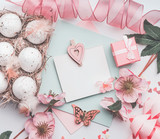 Easter greeting card mock up with eggs box, pink ribbon, gift box and flowers decoration, top view, pastel color - 193789003