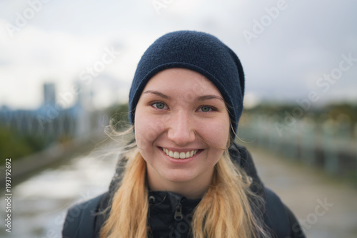 Poster urban portrait of teen girl walking in the city in autumn or spring