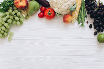 A banner of vegetables and fruits on a wooden white table, flat lay and top view.