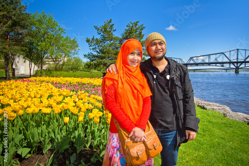 Fotobehang Canada A Muslim couple from Asia taking picture with tulip flowers as background