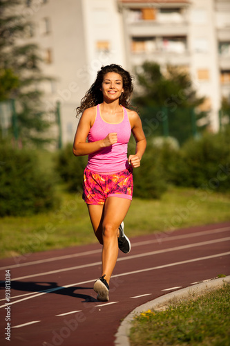 Foto op Canvas Jogging active young woman runs on atheltic track on summer afternoon