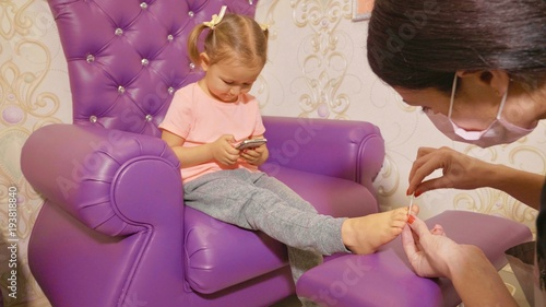 Aluminium Pedicure Cute baby girl using smart phone at pedicure procedure in beauty spa salon