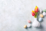 Easter composition with spring tulips flowers in white vase and colored quail eggs candies. Holidays flat lay concept with copy space.