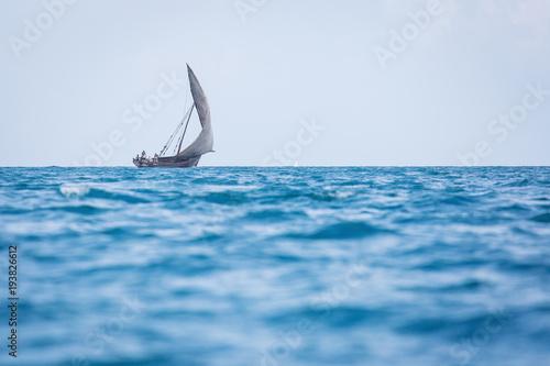 Fotobehang Zanzibar Fishermen going on ocean on traditional fishing boat in Zanzibar with storm clouds at sunrise