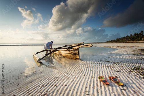 Foto Spatwand Zanzibar Fishermen going on ocean on traditional fishing boat in Zanzibar with storm clouds at sunrise