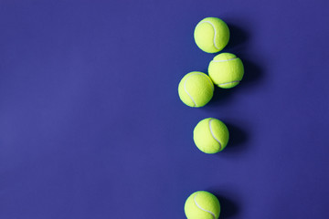Yellow tennis balls on violet background. Concept sport.