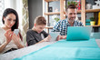 Family with laptop, tablet and smartphone, everyone using digital devices