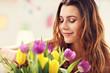 Attractive woman arranging tulips flowers in vase