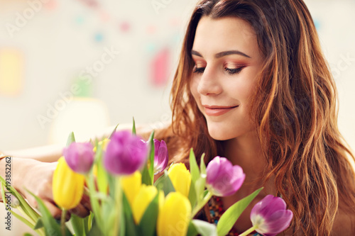 Attractive woman arranging tulips flowers in vase - 193852262