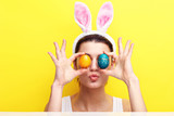Fototapety Happy young woman wearing bunny ears and having Easter Eggs