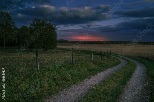 Fotobehang Nachtblauw gravel road in the country leading towards sunset