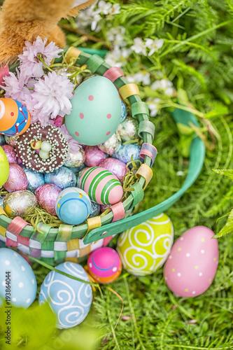 Ostereier im Osterkorb mit Süßigkeiten und Schokolade