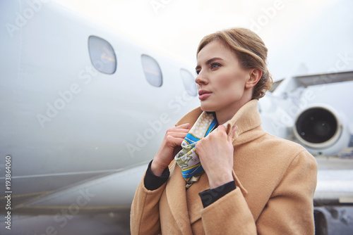 Side view smiling lady straightening coat while standing near aircraft on street. Journey concept