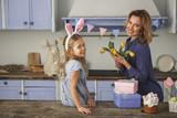 Waist up portrait of pleased woman and her daughter in country style kitchen. Mother is holding bunch of yellow flowers and smiling