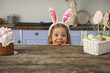 Portrait of joyful female child wearing bunny ears, she is peeking out from behind kitchen table with easter cake and basket with eggs and smiling. Copy space in left side