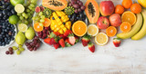 Assortment of fresh fruits and vegetables in rainbow colours on the off white table, top view, selective focus