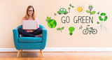 Go Green with young woman using her laptop in a chair