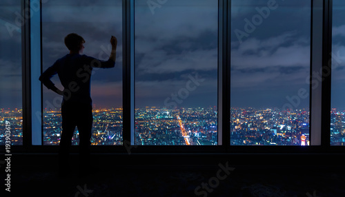 Man writing on large windows high above a sprawling city at night - 193903619
