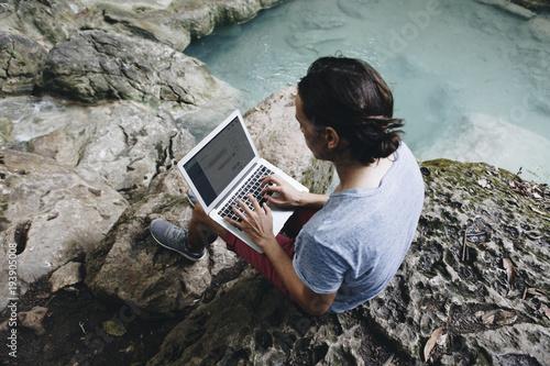 White man using computer laptop at waterfall - 193905008