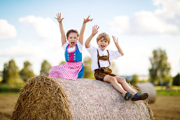 Two kids, boy and girl in traditional Bavarian costumes in wheat field with hay bales
