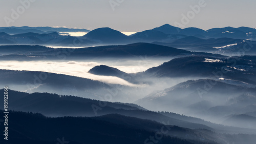 Fotobehang Nachtblauw A frozen morning on top of Ciucas mountains in Romania with some beautiful clouds dancing in the valley bellow