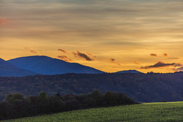 beautiful sunset landscape over the green hills