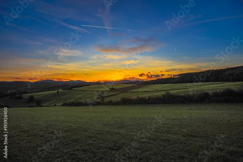 Aluminium Nachtblauw beautiful sunset landscape over the green hills