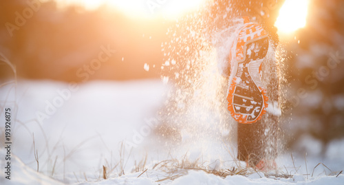 Fototapeta Picture of running man in sneakers on snowy forest in winter