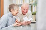 Paar Senioren mit Taschenrechner und Kassenzettel - 193927035
