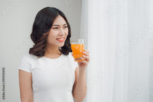 Foto op Canvas Sap Beautiful asian girl drinking a glass of orange juice.