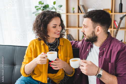 smiling-woman-drinking-coffee-with-boyfriend