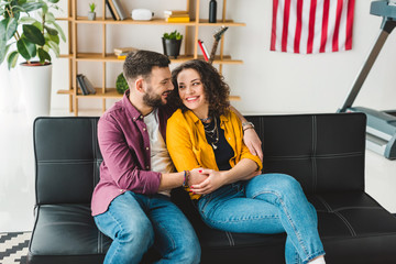 Smiling man and woman holding each other by hands
