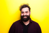 Caucasian bearded hipster smiling on yellow background - 193934400