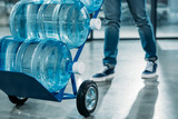 Close-up view of loader man pushing cart with water bottles - 193940411
