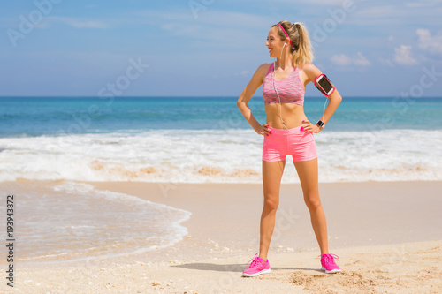 Fit sporty girl standing on the beach